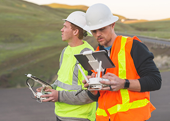 Engineers pilot drones at a worksite.