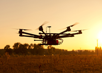 A drone hovers at sunset.