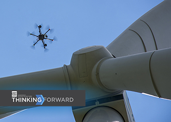 A SkySpecs drone inspects a wind turbine.