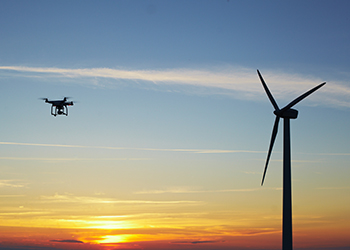 A drone hovers near a wind turbine.